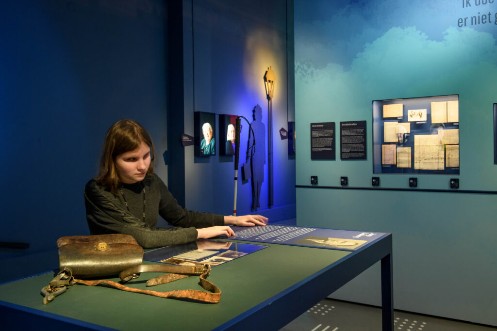 Jonge vrouw leest braille in het Verzetsmuseum.